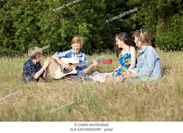 Children playing music together in field