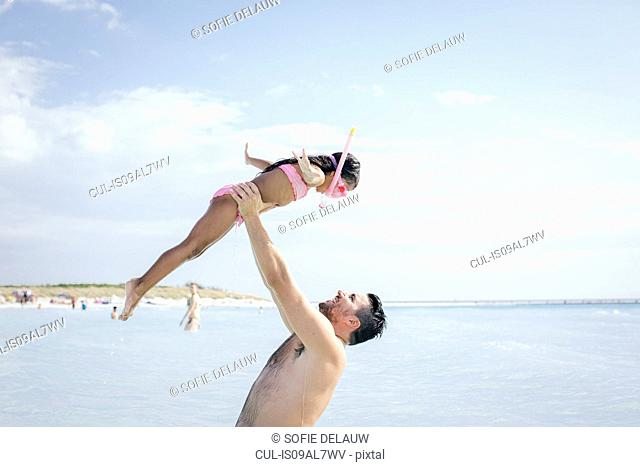 Father holding up snorkeler daughter in sea, Tuscany, Italy