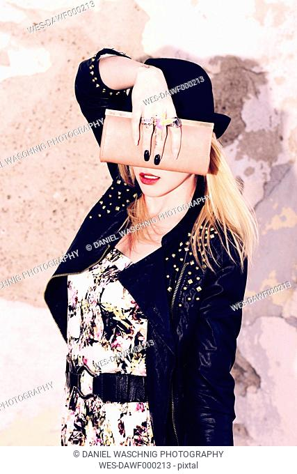 Young blond woman hiding face behind her wallet