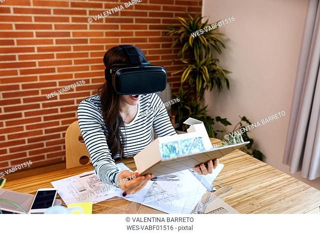 Young woman working in architecture office, looking at model with VR goggles