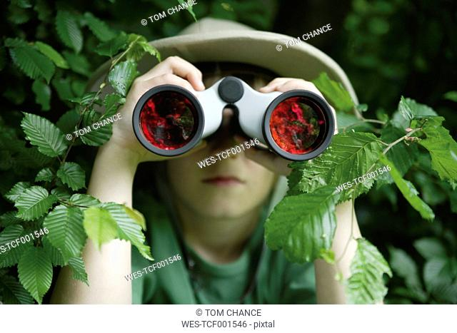 Germany, Bavaria, Close up of boy looking through binocular in forest