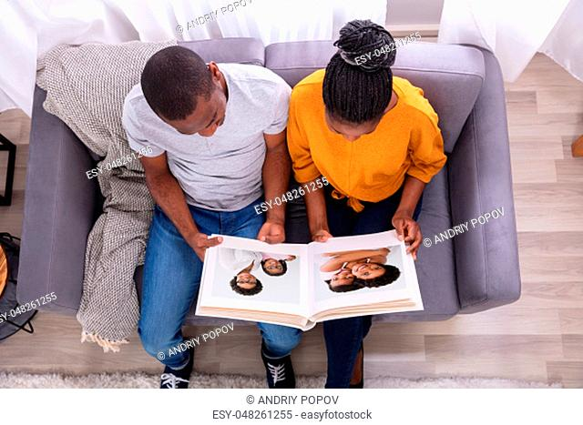 High Angle View Of An African Couple Sitting On Sofa Looking At Photo Album