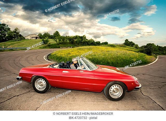 Red Alfa Spider 2000, convertible on winding road, at Castelvetro, Modena, Emiglia-Romagna, Italy