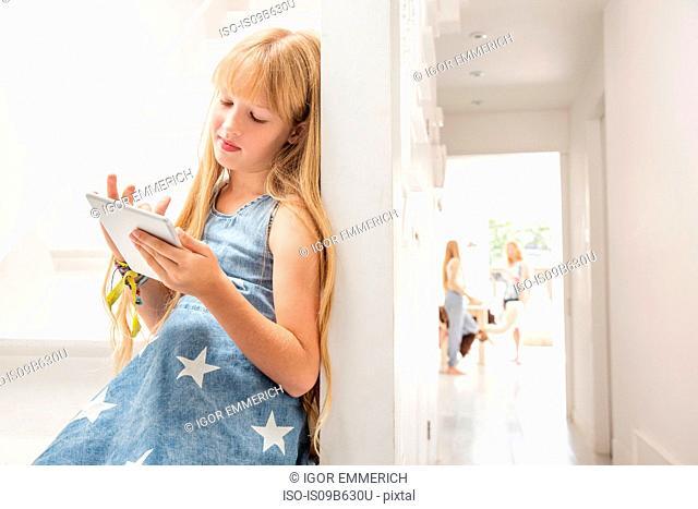 Girl in hallway using digital tablet