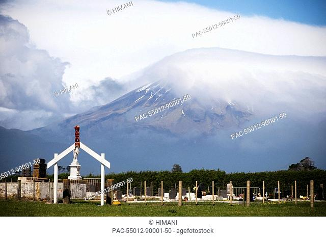 New Zealand, North Island, Taranaki, Maori graveyard with a wooden gateway with red carving figurine in small village, Okato