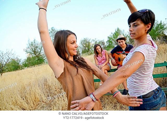 Young man plays the Spanish guitar while her friends dance Sevillanas