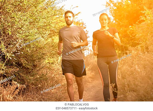 Young friends running down a path in the late afternoon sunshine with trees behind, while wearing casual clothing