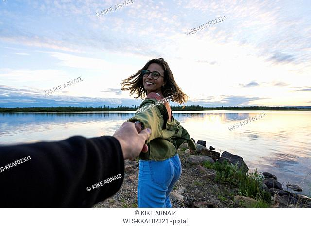 Finland, Lapland, happy young woman holding man's hand at the lakeside at twilight