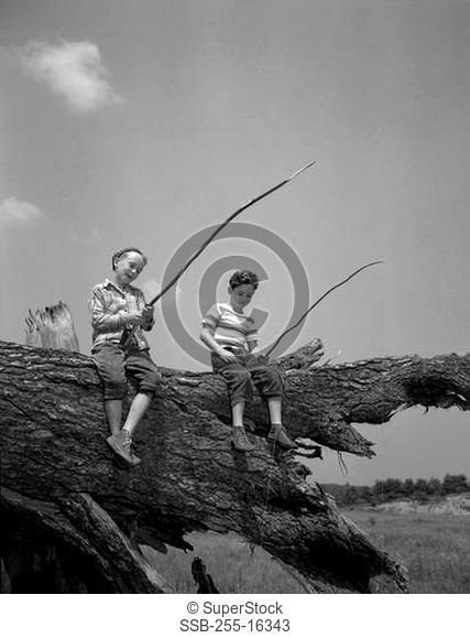 Two boys sitting on tree trunk and fishing with homemade fishing rod