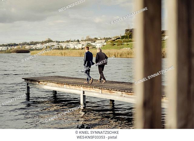 Two businessmen walking on jetty at a lake