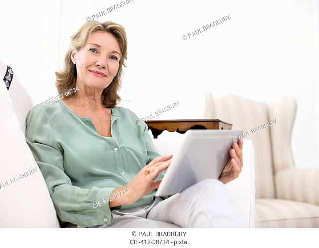 Portrait of senior woman using digital tablet on sofa