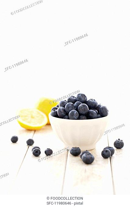 A bowl of fresh blueberries with lemon in the background