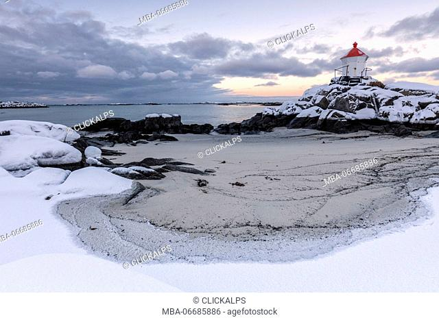 Colorful arctic sunset on the lighthouse surrounded by snow and icy sand Eggum Vestvagoy Island Lofoten Islands Norway Europe