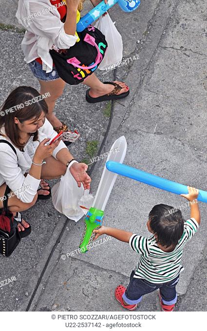 Itoman, Okinawa, Japan: bored mother at the traditional Haarii Boat Festival