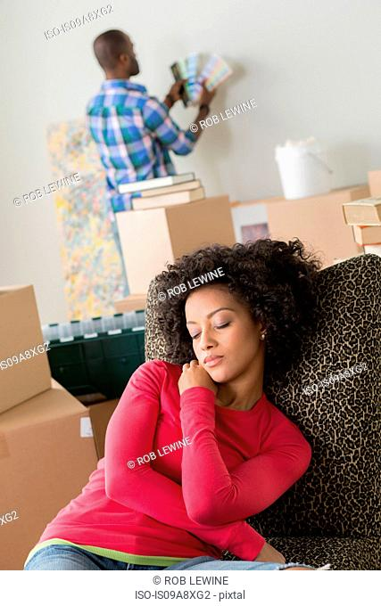 Mid adult woman asleep on chair, man in background
