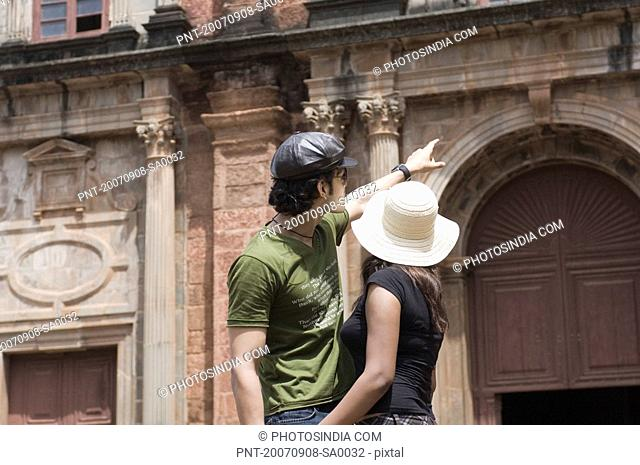 Side profile of a young man standing with a young woman and pointing towards a building, Goa, India