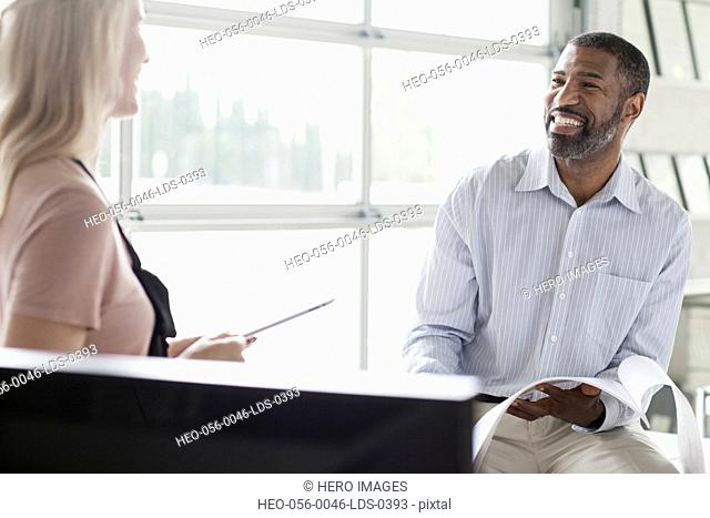 two coworkers sharing a laugh at the office