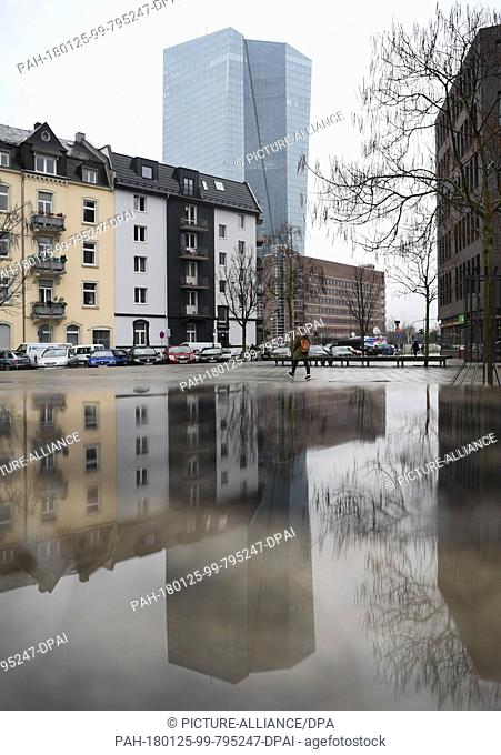 The European Central Bank (ECB) headquarters rising into the sky and being reflected by a puddle in a square in the Ostend district of Frankfurt am Main