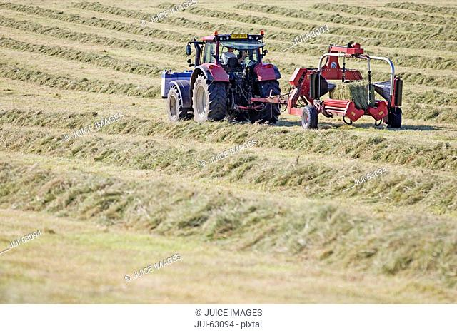 Tractor and bale wrapper wrapping bales of hay in field