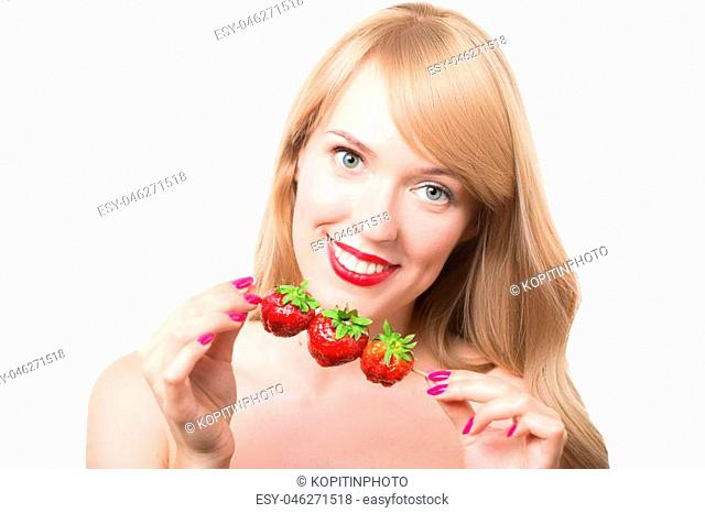 Portrait of young woman with bare shoulders holding ripe strawberry