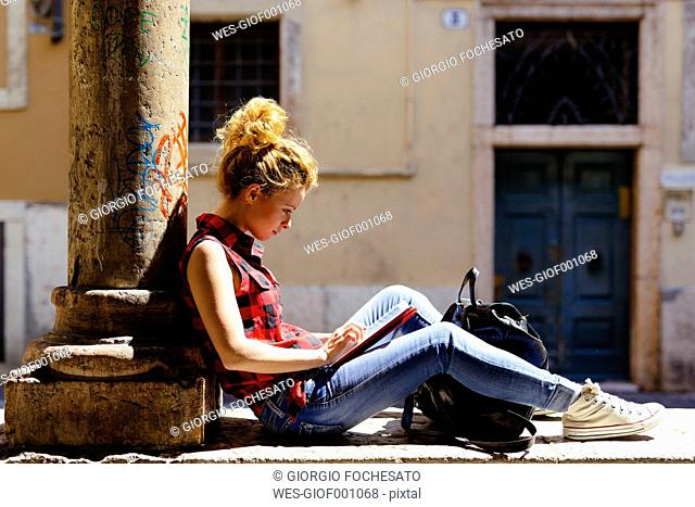 Italy, Verona, woman sitting outdoors using digital tablet