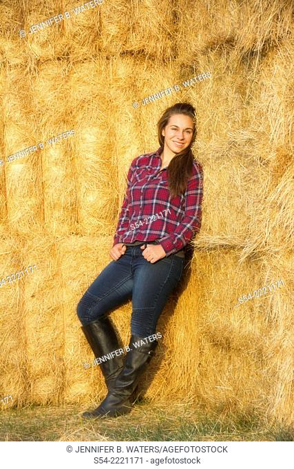 A happy teen girl leans against hay bales at a farm in Eastern Washington, USA