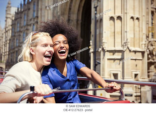 Enthusiastic friends laughing on double-decker bus in London