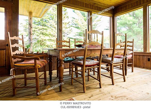 Dining table and chairs, treated wood floorboards inside country home, Quebec, Canada