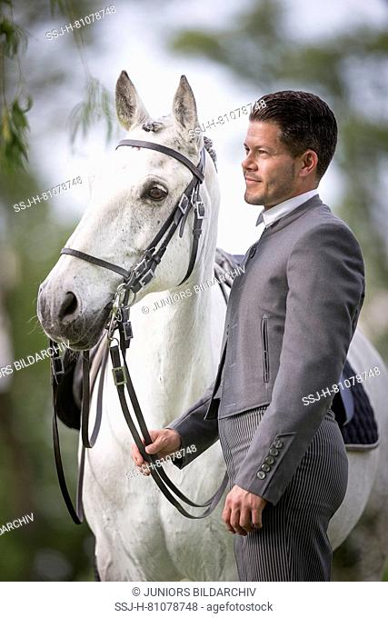 Pure Spanish Horse, Andalusian. Blind gelding Fury standing next to its rider and owner Sandro Huerzeler. Switzerland