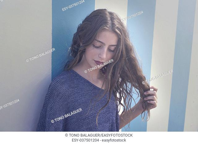 Brunette teen girl portrait in a summer beach blue stripes wall filtered image