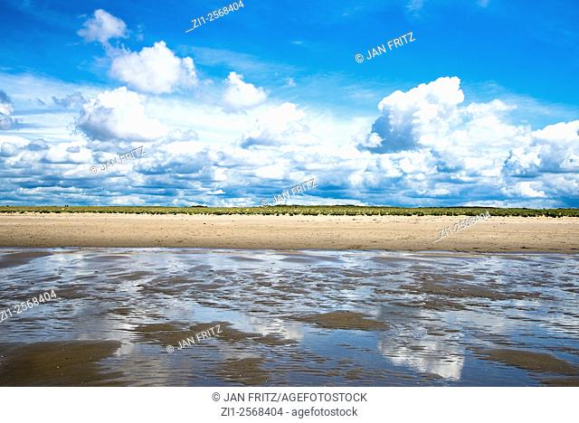 Beach, blue sky and white clouds reflected in water left at low tide in Holland