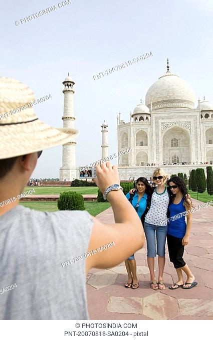Rear view of a young man taking a picture of three young women, Taj Mahal, Agra, Uttar Pradesh, India