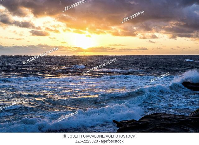 Clouds and the setting Sun over the Pacfiic Ocean. Viewed from Windansea Beach. La Jolla, California, United States