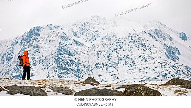 Female climber in front of snow covered mountain, Y Garn, Snowdonia