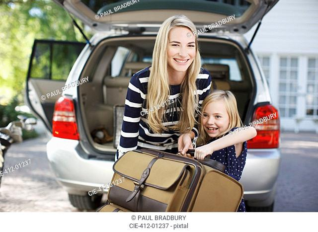 Mother and daughter carrying luggage to car
