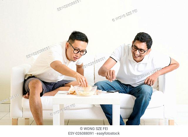 Men talk concept. Two young male friend gathering, chatting and eating at home. Multiracial people friendship