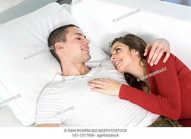 Portrait of a couple at home in love relaxing in the sofa
