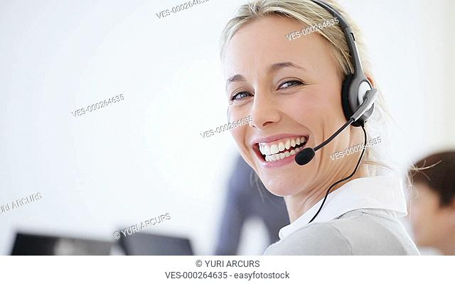 Gorgeous sales representative smiling happily at the camera in her workplace