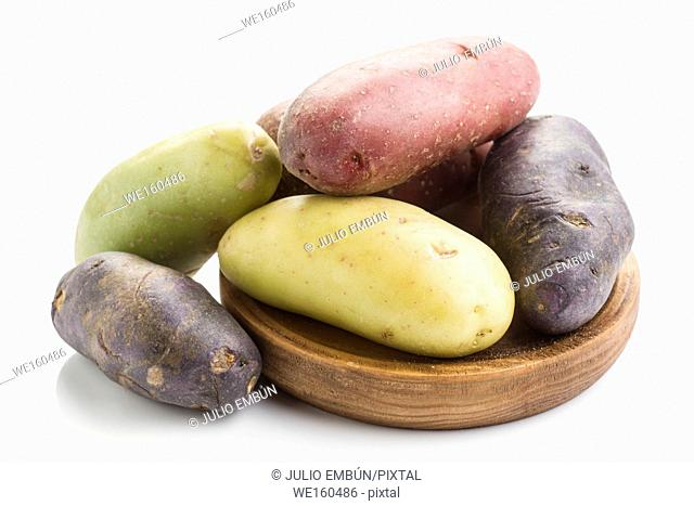 colorful potatoes on wooden board isolated on white
