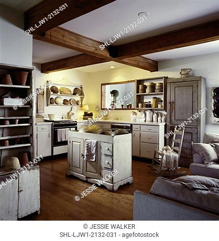 KITCHEN: Primitive monochromatic white with antique finish cabinets, wood floor, wooden bowls, pantry boxes, exposed natural beams