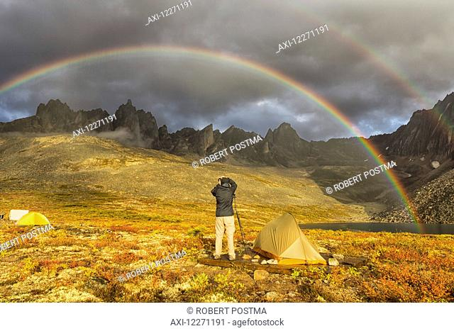 Photographer taking pictures of the late afternoon light hitting the mountains in the Tombstone Territorial Park of the northern Yukon; Yukon, Canada