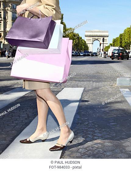 A woman carrying shopping bags walking across a zebra crossing, Paris, France