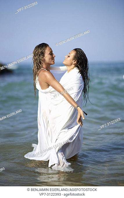 two women shrouded in white blanket sheet, standing in sea, best friends, looking at each other, holiday. Chersonissos, Crete, Greece