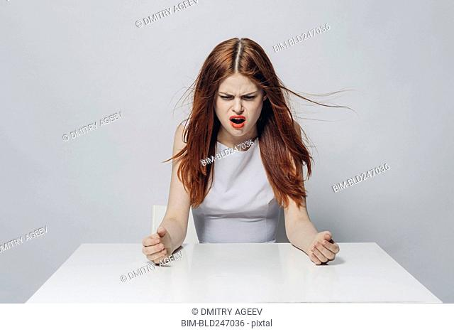 Angry Caucasian woman sitting at windy table