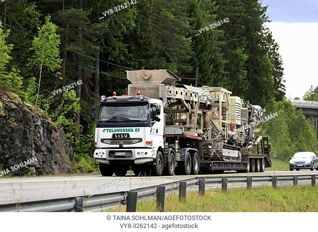 Sisu semi trailer of Telamurska Oy transports Metso Lokotrack crusher on scenic road. The machinery weighs 100000 kg. Salo, Finland - June 30, 2018