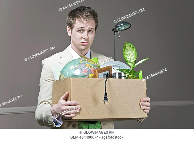 Fired businessman holding his office belongings