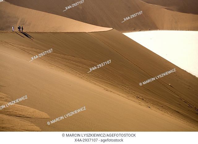 Tourists walking on the edge of a dune, Namib desert near Soussuvlei, Namib-Naukluft National Park, Namibia