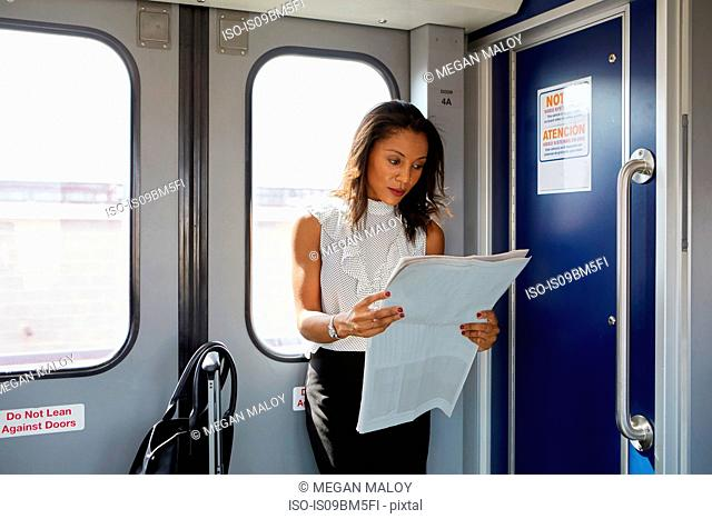 Businesswoman reading newspapers on train