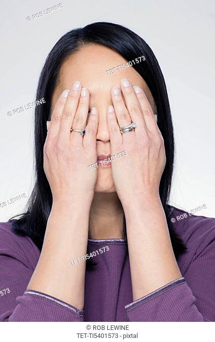 Studio portrait of mature woman covering eyes
