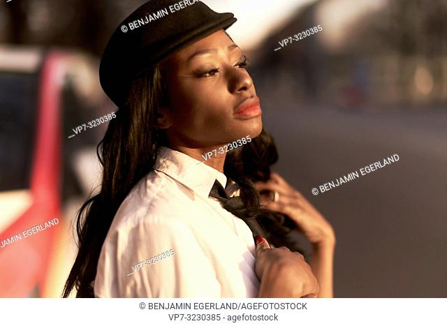 stylish woman wearing retro business outfit at street in evening sunlight, closed eyes, sensual mood, African Angolan descent, in city Munich, Germany